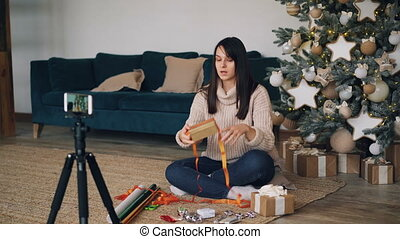 Smiling young lady vlogger is recording video about gift wrapping teaching subscribers to decorate present boxes with ribbons sitting on floor near Christmas tree.