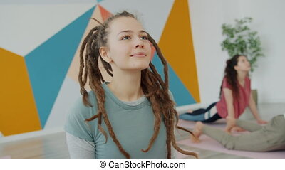 Smiling young lady with dreadlocks exercising in yoga class ...