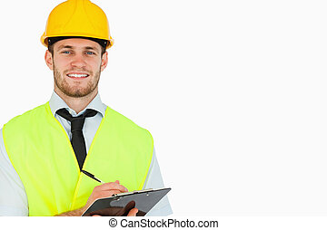 Smiling young lead worker with clipboard against a white...