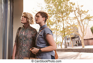 Smiling young lesbian couple enjoying a day shopping together