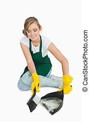 Smiling young maid using brush and dust pan over white...