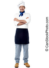 Smiling young male chef with arms crossed