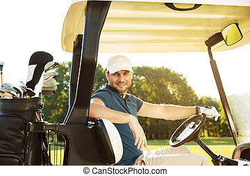 Smiling young male golfer sitting in a golf cart