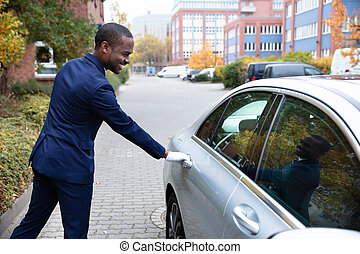 Smiling Young Male Valet Opening Car Door - Side View Of...