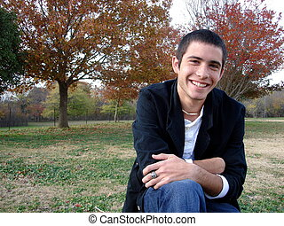 Smiling Young Man - A young man smiling while sitting on a...