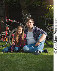 Smiling young man and cute girl relaxing on grass at park after riding bicycles