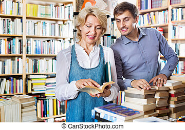 Smiling young man and mature woman holding books - Smiling ...