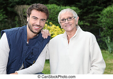 smiling young man and older woman in garden