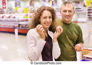 Smiling young man and woman buy peaches in supermarket