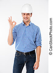 Smiling young man builder in hard hat showing ok gesture