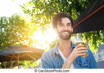 Smiling young man drinking beer at outdoor bar in summer