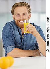 smiling young man drinking orange juice