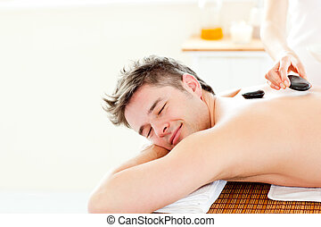 Smiling young man enjoying a back massage with hot stone