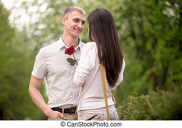 Smiling young man giving flower