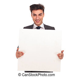 smiling young man holding a blank board