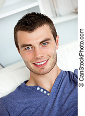 Smiling young man holding a remote