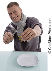 smiling young man holding fork and knife