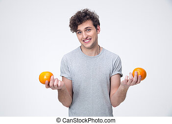 Smiling young man holding orange over gray background