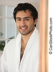 Smiling  young man in a bathrobe