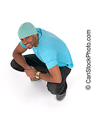 Smiling young man in a blue t-shirt squatting