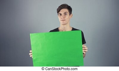 Smiling Young man in black shirt holding green key sheet poster gray background