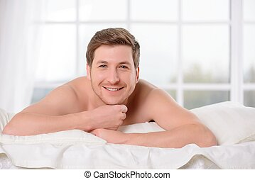 Smiling young man lays awake in bed.