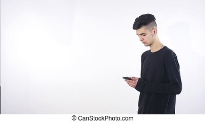 Smiling young man looking at his smart phone while text messaging isolated on white background