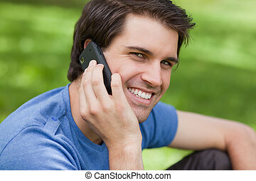 Smiling young man looking at the camera while using his mobile phone in a parkland