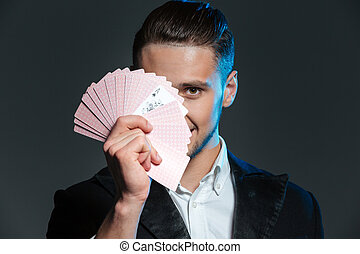 Smiling young man magician covered his face with playing...