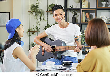 Smiling young man playing guitar for friends