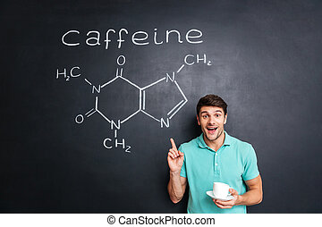 Smiling young man pointing on drawn caffeine molecule chemical structure