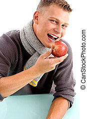 smiling young man posing with apple