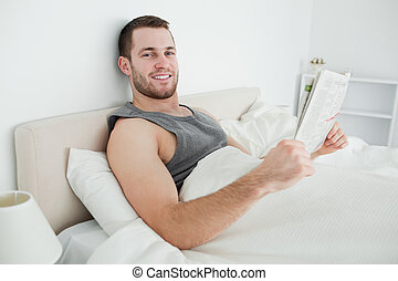 Smiling young man reading a newspaper