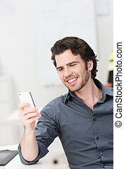 Smiling young man reading an sms on his mobile