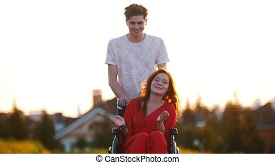 Smiling Young Man Rolls A Red-Haired Girl On A Wheelchair,...