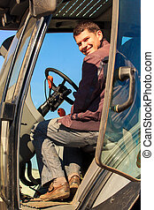 smiling young man sits in cab of tractor