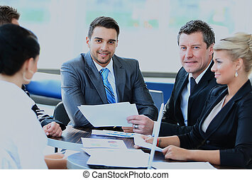 Smiling young man sitting at a business meeting with colleagues.