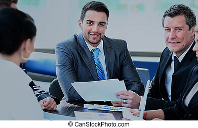 Smiling young man sitting at a business meeting with colleagues