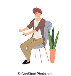 smiling young man sitting on a chair next to a pot