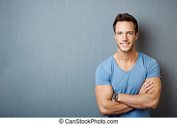 Smiling Young Man Standing With Arms Crossed