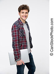 Smiling young man standing with laptop over gray background