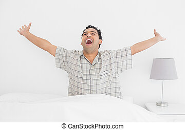 Smiling young man stretching his arms in bed