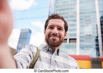 Smiling young man taking a selfie in the city
