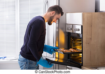 Smiling Young Man Taking Out Tray Of Croissants From Oven