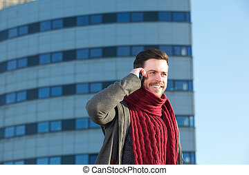Smiling young man talking on cellphone in the city