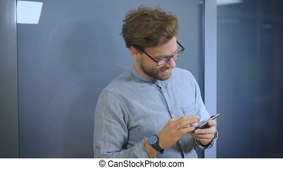 Smiling young man texting on the cellphone