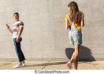 young man turning around to see young woman on street