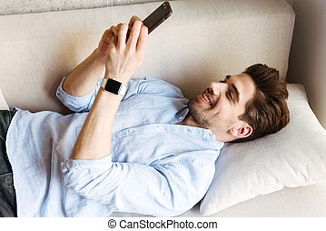 Smiling young man using mobile phone while laying