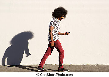 smiling young man walking on sidewalk with mobile phone