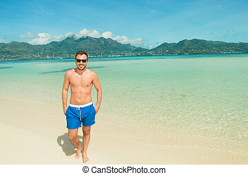 man walking on the beach with hands in pockets